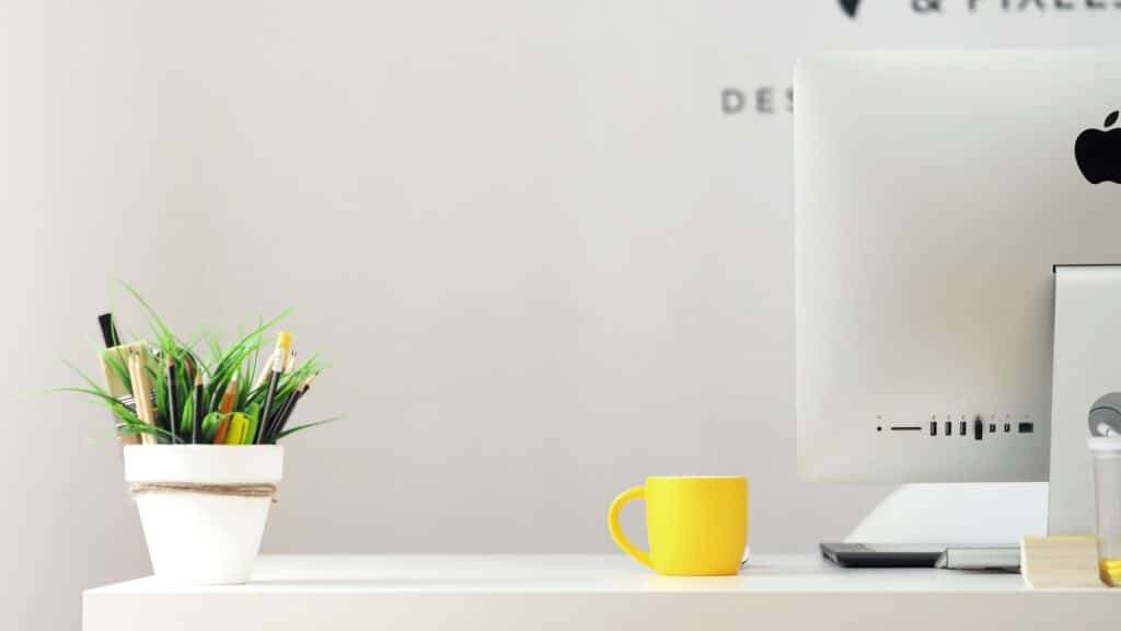 Desk with bright yellow mug and green plants. Workplace wellness with added green space to office.