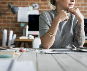 Young Millennial or Gen-Z professional woman with tattoos and a thoughtful expression, sitting in a modern office and working independently